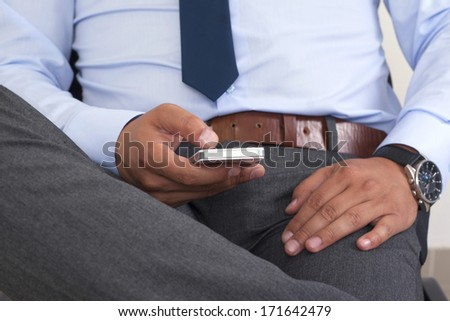 Hands of a man using a smartphone.