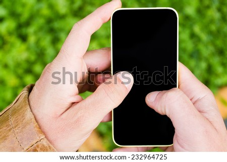 Hands of a man using a smartphone - stock photo