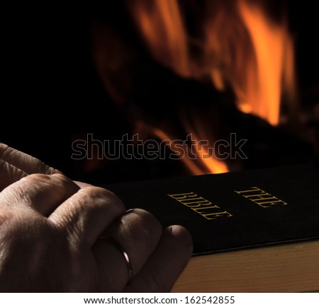 Hands of a man with a Bible on fire background - stock photo