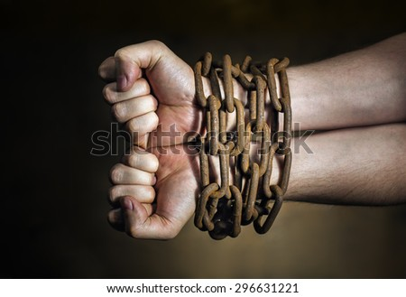 Hands of a man with a rusty chain around the wrists. - stock photo