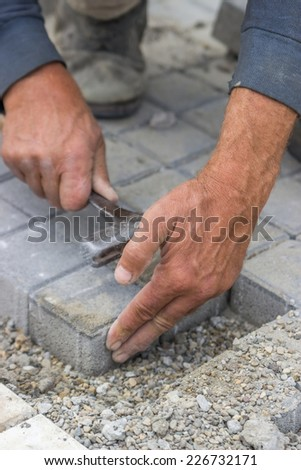 Hands of a manual worker laying concrete brick pavers