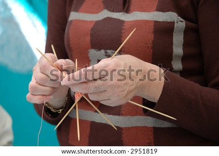 Hands of a mature lady knitting an orange scarf