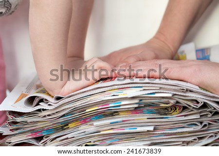Hands of a mother and her child collecting newspapers for recycling - stock photo