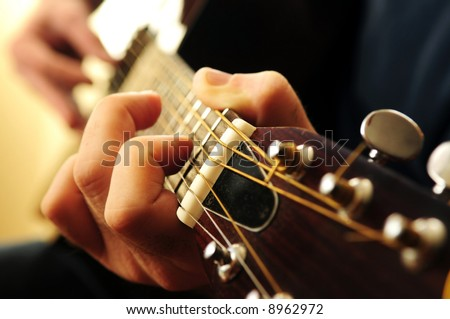 Hands of a person playing an acoustic guitar close up - stock photo
