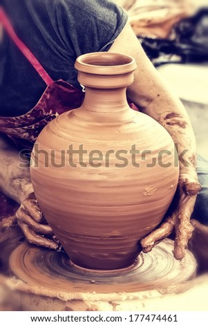 Hands of a potter, creating an earthen jar. Cross processing - stock photo