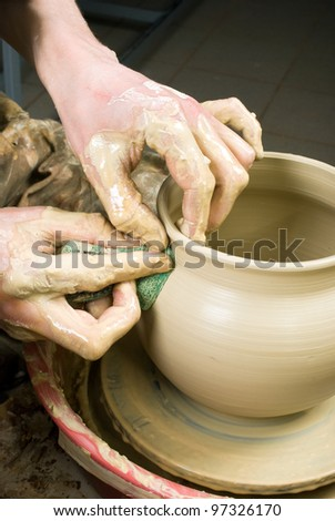 hands of a potter, creating an earthen jar of white clay
