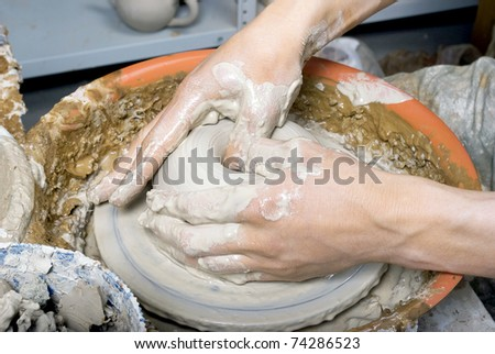 hands of a potter, creating an earthen jar on the circle - stock photo