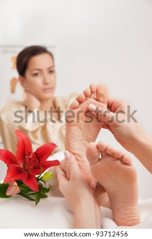 Hands of a reflexologist doing reflexology treatment on the soles of a womans feet - stock photo