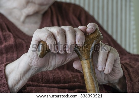 hands of a senior person holding walking stick - stock photo