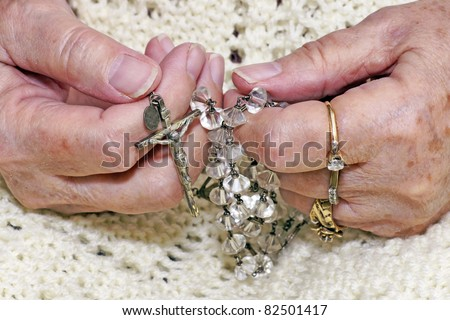 Hands of a senior woman holding a vintage crystal rosary to pray. - stock photo