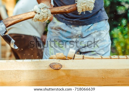 Hands of a strong man splitting wood with an axe, focus is on the axe, motion freezing in the moment it split