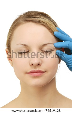 Hands of a surgeon touching the face of a beautiful woman - stock photo