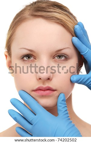 Hands of a surgeon touching the face of a beautiful woman, closeup - stock photo
