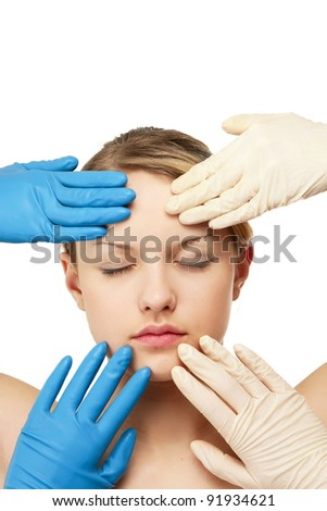 Hands of a surgeon touching the face of a beautiful woman, isolated on white background - stock photo