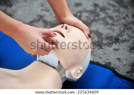 Hands of a woman are seen on a mannequin during an exercise of resuscitation - stock photo