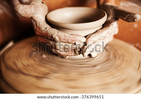 Hands of a woman creating a clay jar on a potter's wheel - stock photo