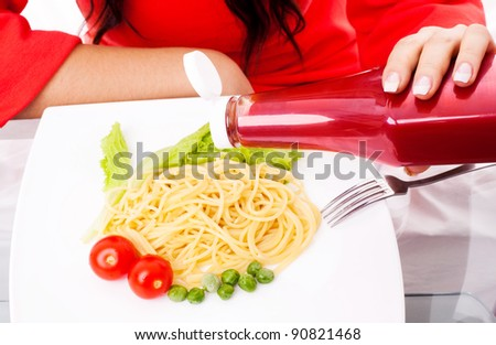 hands of a woman eating spaghetti with tomatoes, salad and peas and adding ketchup - stock photo