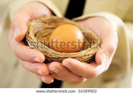 Hands of a woman holding a nest with an egg