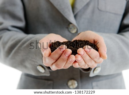 Hands of a woman in business suit  holding a handful of earth against white background