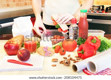 Hands of a woman is making school lunch box in the red color. It is more interesting for children. Caucasian female preparing food (fruits and vegetables) for healthy eating child (kid). - stock photo