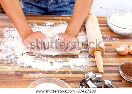 Hands of a woman making dough in the kitchen