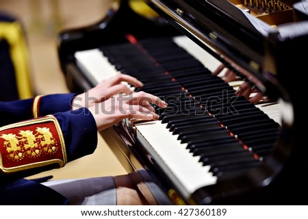 Hands of a woman part of a military orchestra performing at a piano during a concert - stock photo