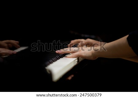 Hands of a woman playing the piano - stock photo