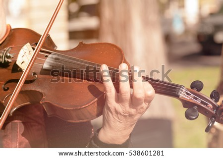 hands of a woman playing the violin