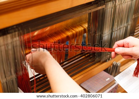Hands of a woman who weaves on a loom - stock photo