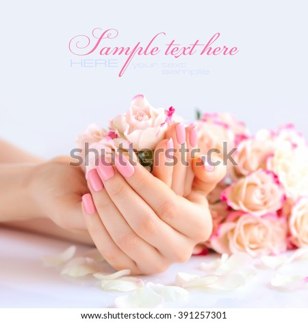Hands of a woman with pink manicure on nails and roses - stock photo