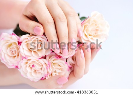 Hands of a woman with pink roses against white background - stock photo