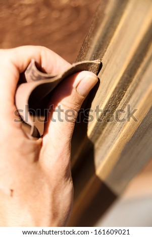 Hands of a woman with sandpaper doing DIY work on wooden fixtures