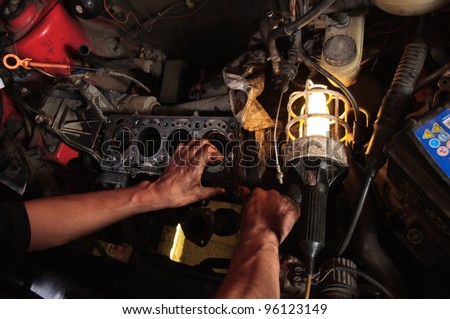 Hands of a worker repairing car interior - stock photo