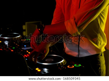 Hands of a young disc jockey scratching and mixing music with vinyl discs on the turntables of his deck - stock photo