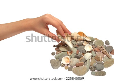 hands of a young girl folding beautiful stones and shells - stock photo