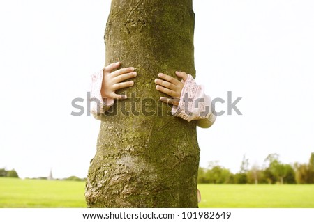 Hands of a young girl hugging a tree in the park while hiding behind the trunk. - stock photo