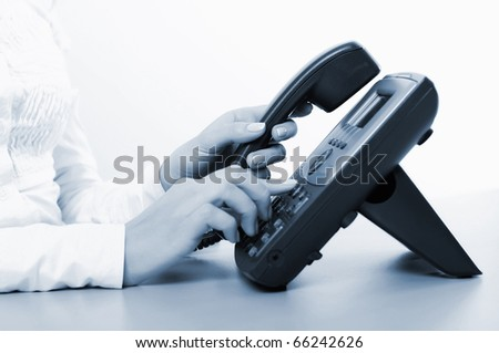 Hands of a young girl on the phone dials the number - stock photo