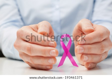 Hands of a young woman around a pink ribbon, international symbol of breast cancer awareness. - stock photo