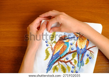 Hands of a young woman embroidering cross picture - stock photo
