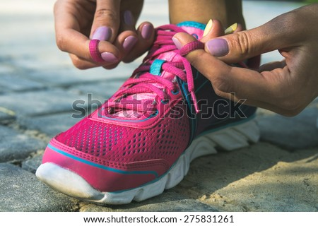 Hands of a young woman lacing bright pink and blue sneakers. Shoes standing on the pavement of stones and sand. In female hands purple-yellow manicure. Photographed close-up. - stock photo