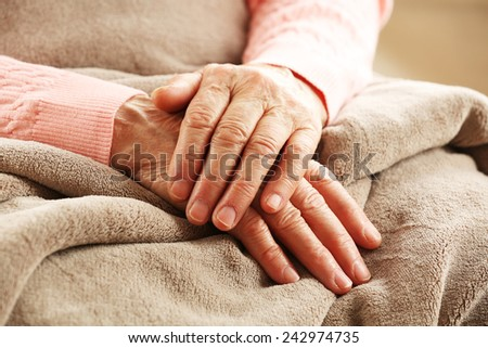 Hands of adult woman on light background, closeup