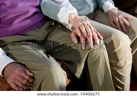 Hands of affectionate elderly couple touching on knee - stock photo