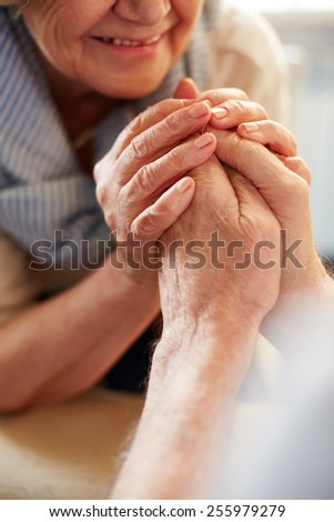 Hands of affectionate seniors - stock photo