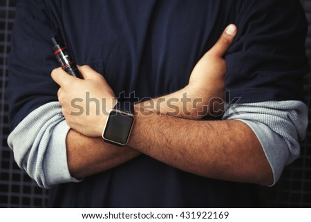 Hands of African model wearing smart wrist watches and holding vaporizer.Modern gadget that lets you always stay connected to internet,social media from everywhere and trendy e-cigarette - stock photo