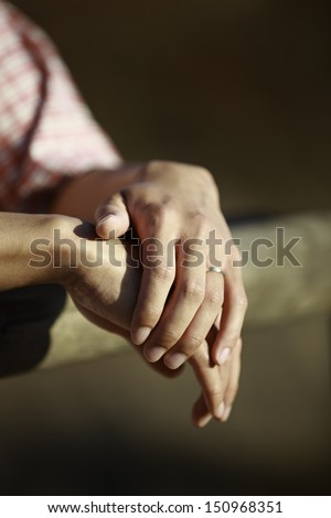 Hands of an Asian man wearing wedding ring