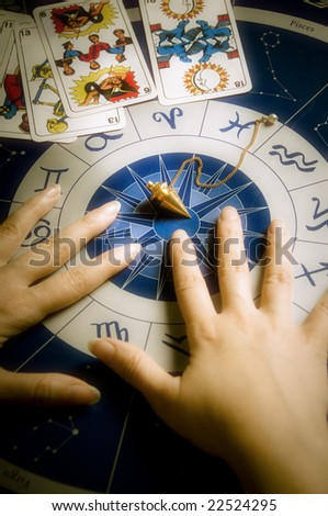 hands of an astrologer over an astrological wheel with tarots and pendulum - stock photo