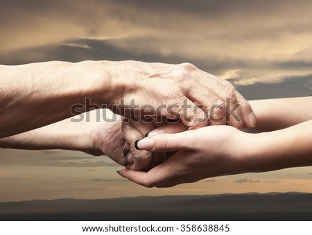 Hands of an elderly senior holding the hand of a younger woman