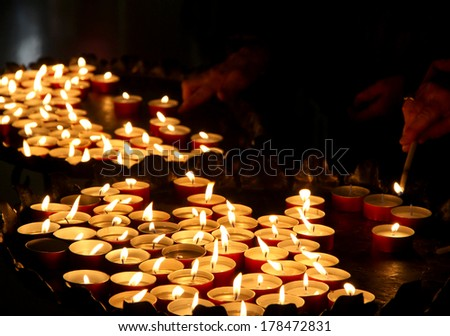 hands of an elderly woman lighting a candle in a church - stock photo
