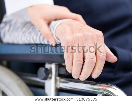 Hands of an elderly woman resting on the wheelchair - stock photo