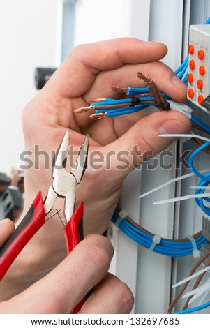 Hands of an electrician with tools at an electrical switchgear cabinet - stock photo
